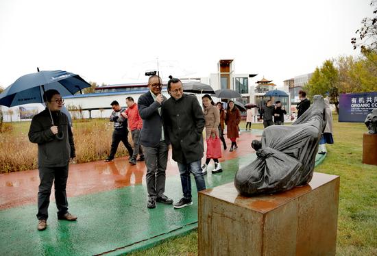 北大资源副总裁林渊先生、艺术家唐华伟、中科院研究员陈涌海先生雨中欣赏雕塑家卢征远雕塑作品
