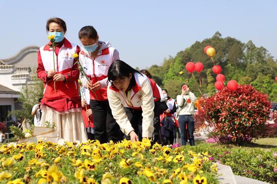 志愿者向4044位捐献大爱者献上鲜花。白洁 摄