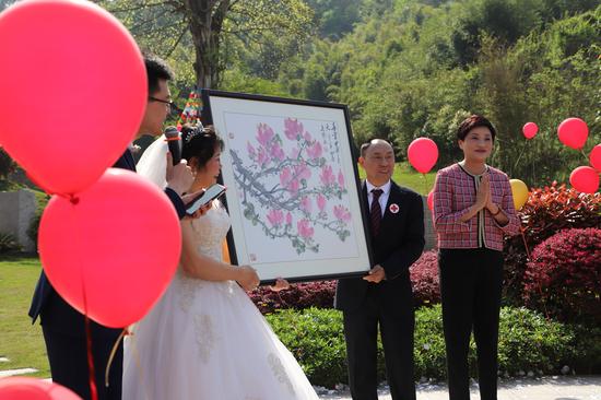 中国殡葬协会专家委员会主任伊华为这对新婚夫妇带来了一幅玉兰图作为礼物。白洁 摄
