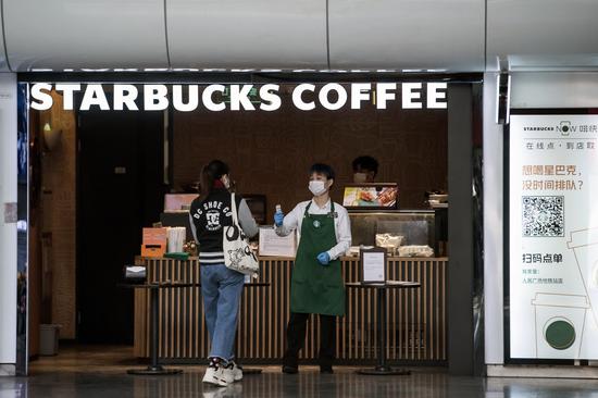 3月2日,上海,一名星巴克員工在店門口測量一名顧客的體溫