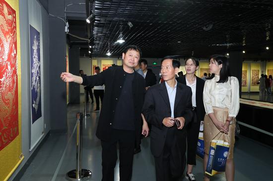 著名刻纸艺术家李艺发先生向中国文化信息协会会长黄河浪介绍刀刻画