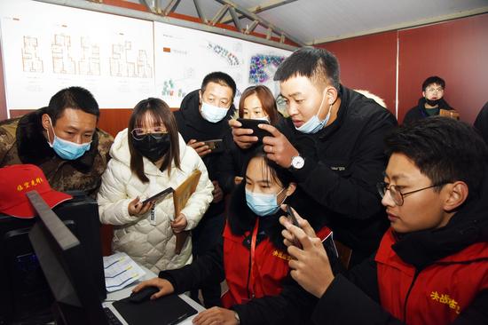 图为村民们正在拍照留存自己选房的信息
