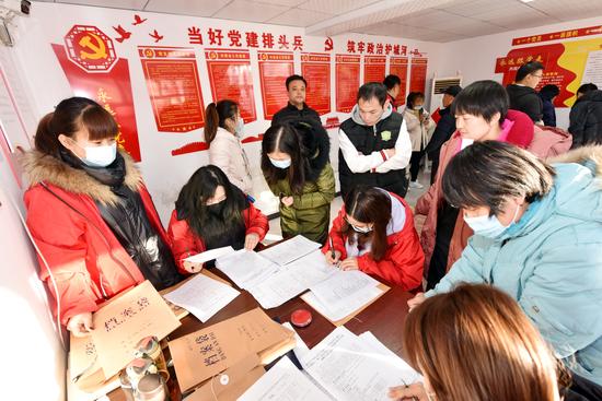 图为工作组正在为村民修改选房方案
