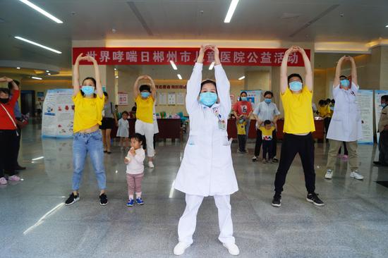 在义诊现场,工作人员们带着小朋友们跳呼吸康复操,小朋友们兴致高昂。
