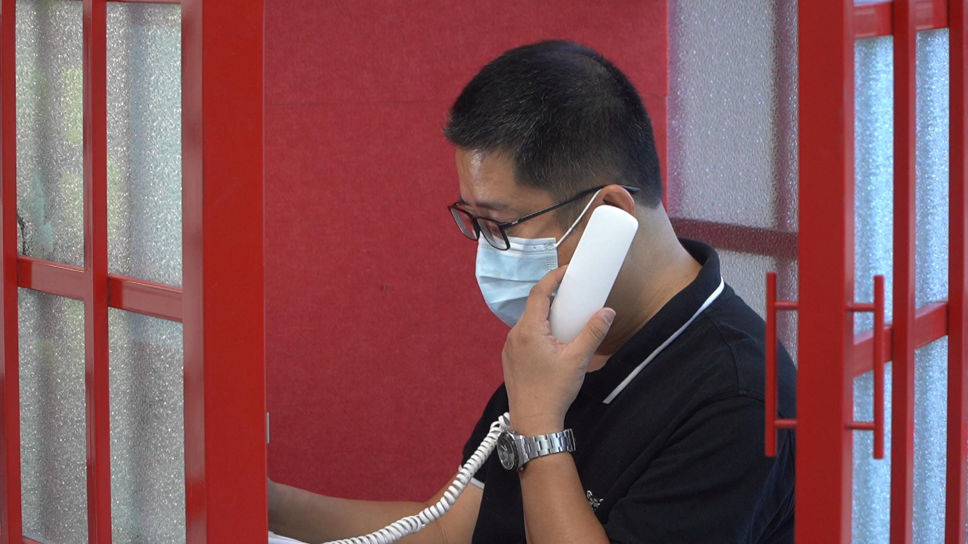 崔洪臣在中秋电话亭给88岁的母亲打电话。新京报记者袁静新 周的